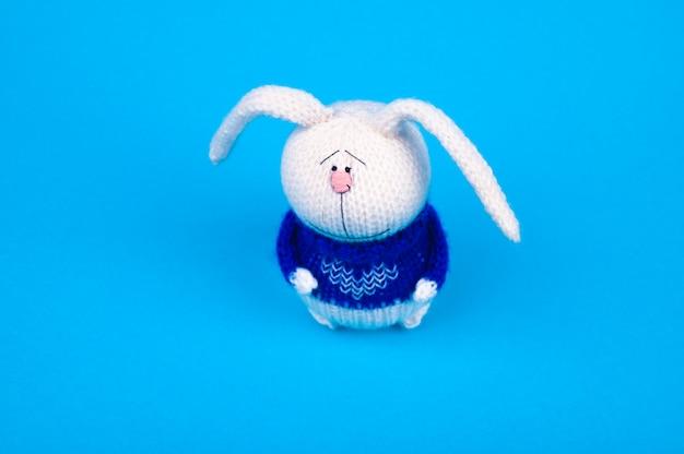 Coelho de malha branco, em um casaco azul com um coração, sobre um fundo azul. coelho com um coração. lugar para escrever.