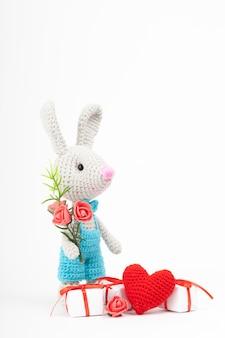 Coelho de malha com um coração. decoração de são valentim. brinquedo de malha, amigurumi, cartão de felicitações.