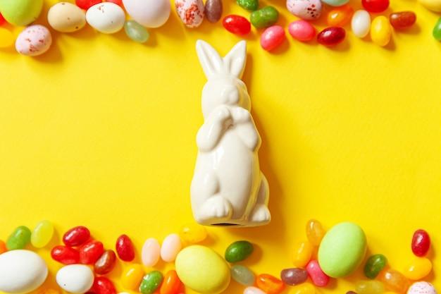 Coelho de ovos de chocolate de doces de páscoa e jujubas isoladas em fundo amarelo