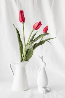 Coelho de páscoa perto de ramo de flores em vaso