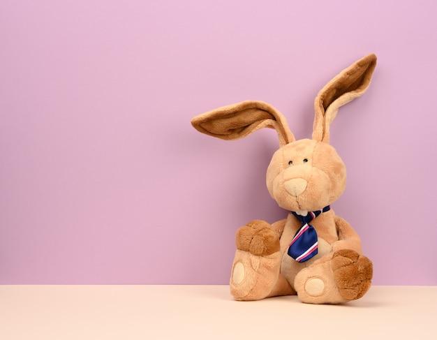Coelho de pelúcia bege engraçado com orelhas grandes e cara engraçada, copie o espaço