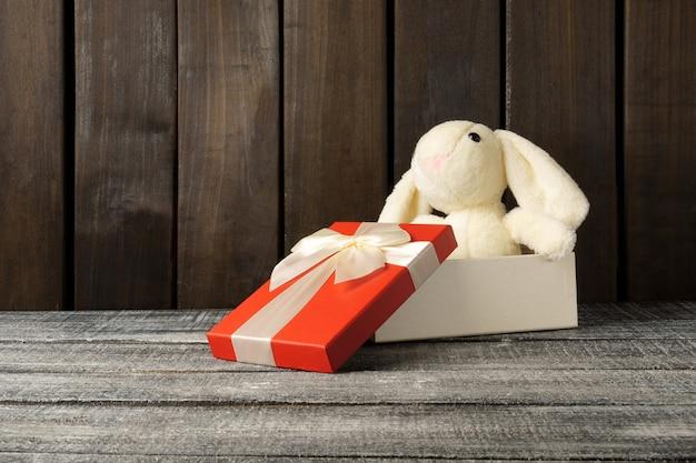 Coelho de pelúcia sentado em uma caixa de presente em uma mesa de madeira escura. brinquedo como um presente.