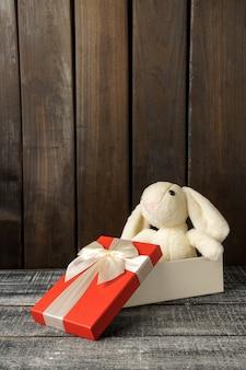 Coelho de pelúcia sentado em uma caixa de presente em uma mesa de madeira escura