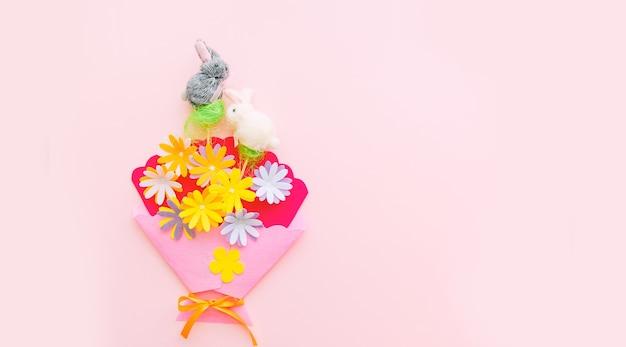 Coelho e flores artesanais no fundo rosa no dia da páscoa. comemorando a páscoa na primavera. espaço para texto.