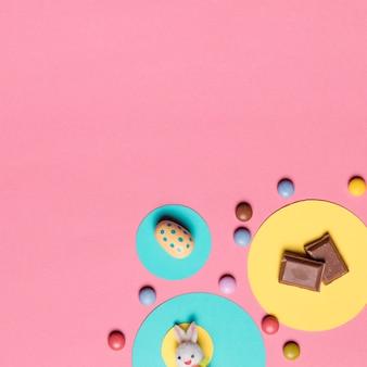 Coelho; ovos de páscoa; pedaços de chocolate e doces gema colorida no fundo rosa