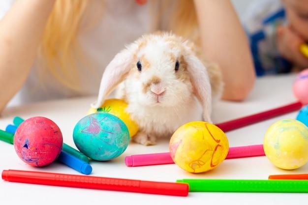 Coelho pequeno do coelho com ovos e os marcadores coloridos na tabela. prepearing para a páscoa, família e feriados conceito.