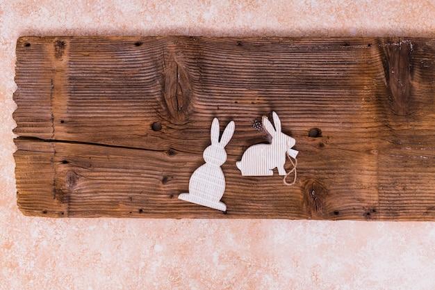 Coelhos brancos pequenos na placa de madeira