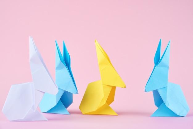Coelhos de esater de origami colorido de papel em um fundo rosa. conceito de celebração da páscoa