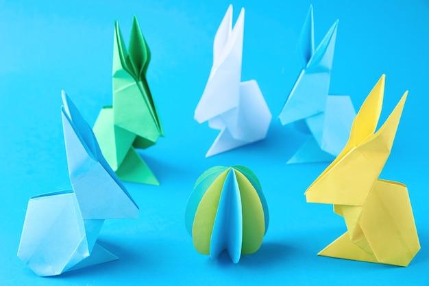 Coelhos de esater de origami de papel e ovos coloridos sobre um fundo azul. conceito de celebração da páscoa