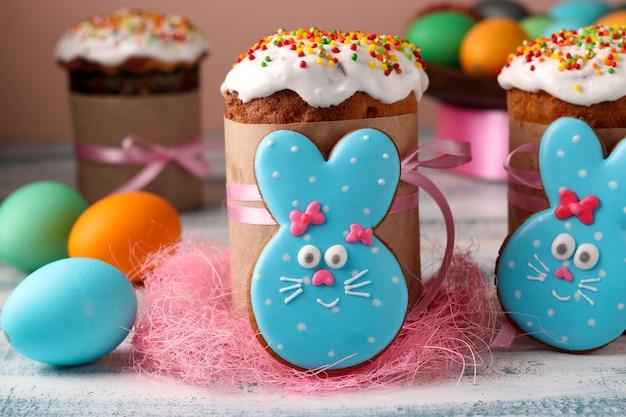 Coelhos engraçados da páscoa, biscoitos caseiros pintados de gengibre com cobertura e bolos de páscoa, ovos coloridos para um feriado de primavera brilhante