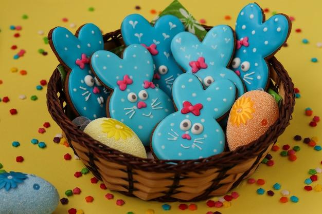 Coelhos engraçados de páscoa, biscoitos de gengibre pintado caseiro em esmalte em amarelo, vista superior