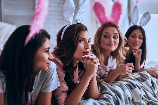Coelhos loucos. quatro mulheres atraentes em orelhas de coelho sorrindo enquanto deitavam na cama
