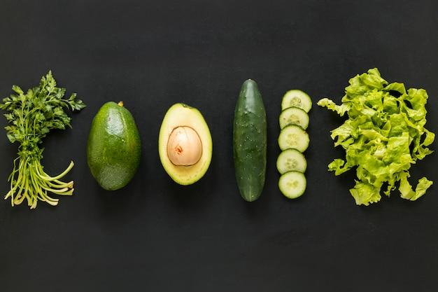 Coentro de linha; abacate; pepino e alface dispostos em pano de fundo preto