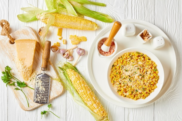 Coentro de milho parmesão em uma tigela branca em uma mesa de madeira branca com ingredientes em uma mesa de madeira branca, vista horizontal de cima, camada plana