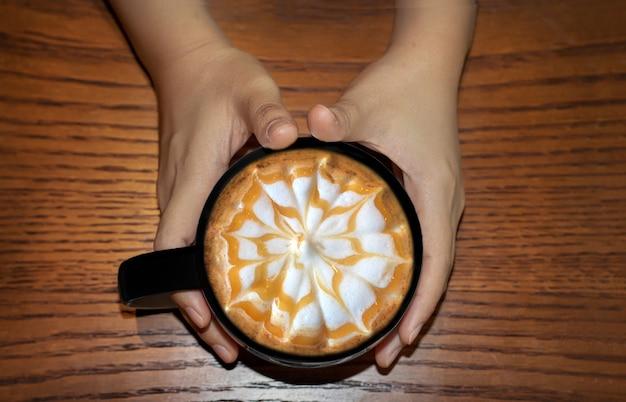 Coffe latte art com syrub marrom na caneca de café com as mãos em volta da mesa de madeira
