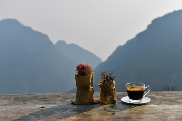 Coffee americano em uma xícara de café transparente ao lado de um vaso de flores com uma montanha ao fundo.