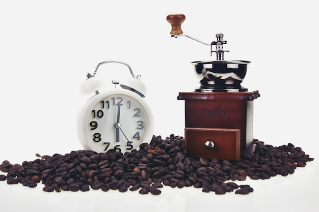 Coffee bean placement moedor de café e relógio às 6 da manhã em um fundo branco.