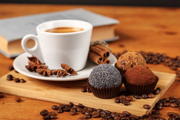 Coffee break. café quente no copo e bolos em uma mesa de madeira. café expresso, livro aberto, grãos de café, canela, anis
