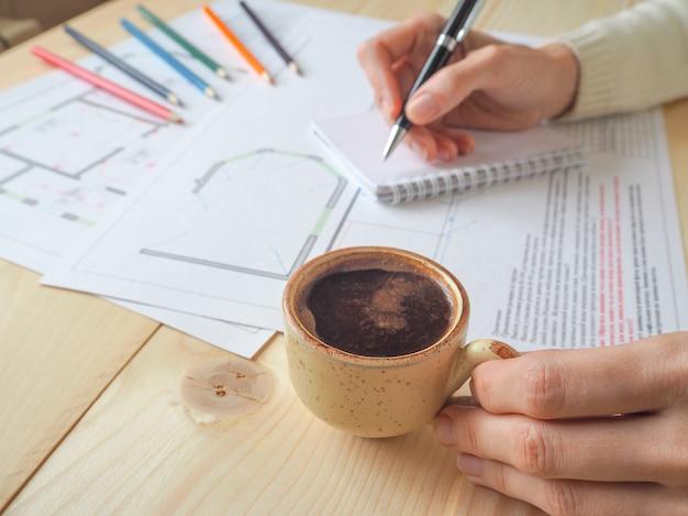 Coffee-break, uma xícara de café durante uma pausa no trabalho. o conceito de negócio da construção de esquemas em um escritório de arquitetura.