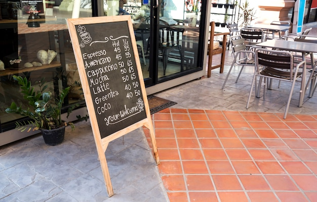 Coffee shop e restaurante com placa preta mostram item e assentos