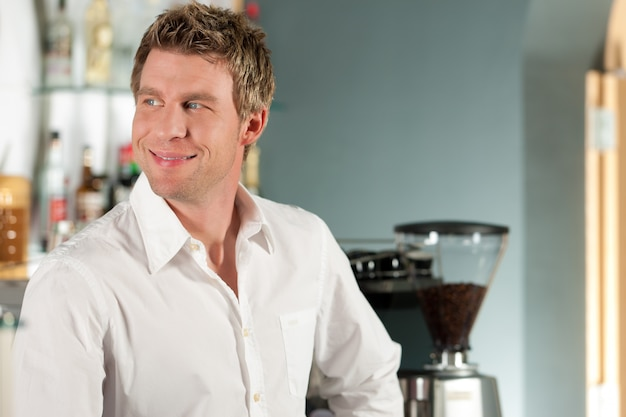 Coffeeshop - barista no café dele, no fundo a máquina de café