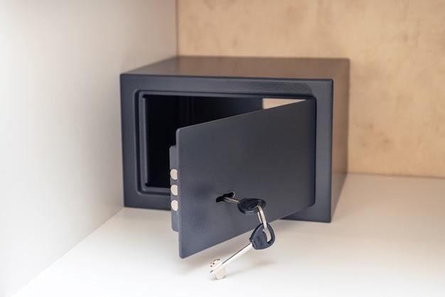 Cofre de metal aberto com chave e porta aberta no quarto de hotel, dentro do armário