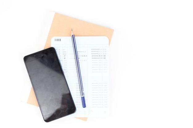 Cofrinho azul com pilha de lápis e moedas em um livro de contas fechado com fundo de telefone celular
