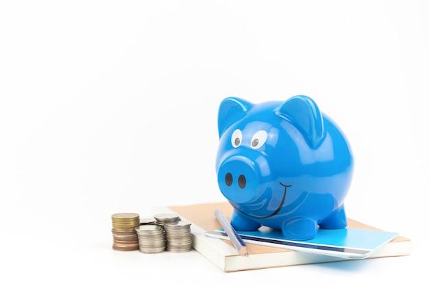Cofrinho azul com pilha de moedas no fundo branco do livro de contas