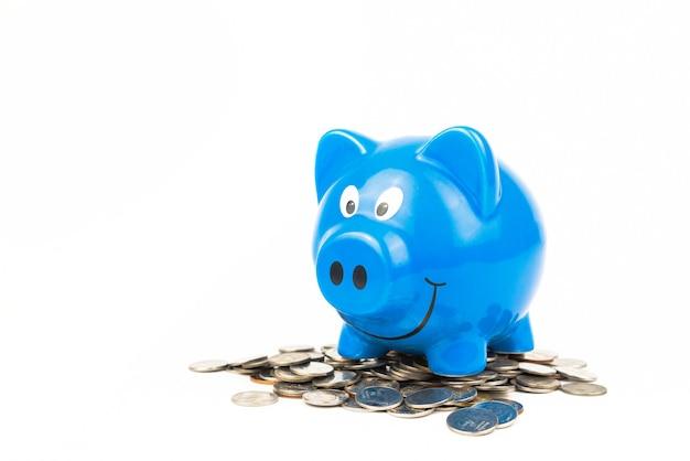 Cofrinho azul com pilha de moedas no fundo branco economia de finanças e conceito de riqueza de dinheiro