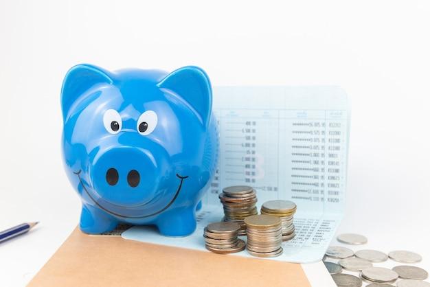 Cofrinho azul com pilha de moedas no livro de conta aberta