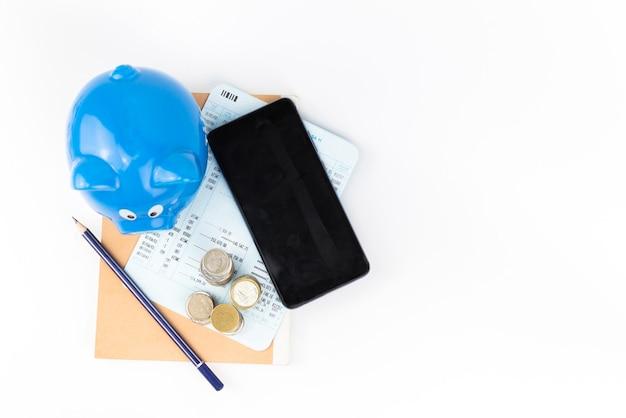 Cofrinho azul com pilha de moedas no livro de contas com fundo do telefone móvel