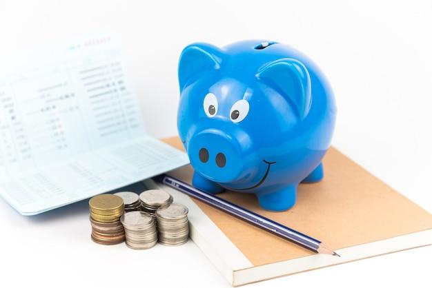 Cofrinho azul com pilha de moedas no livro e fundo branco do livro de contas