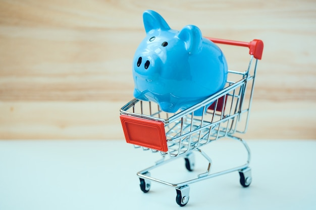 Cofrinho azul no carrinho de compras de brinquedo pequeno