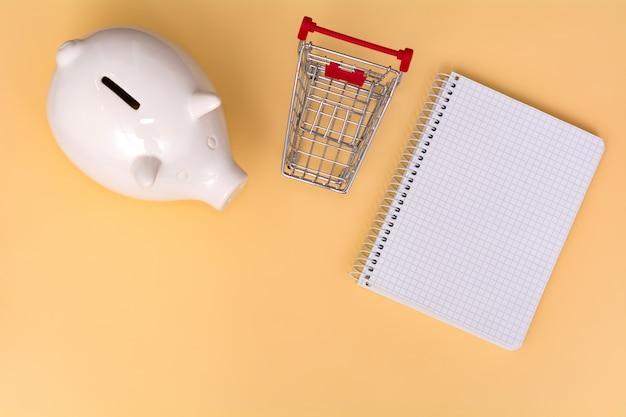 Cofrinho branco, carrinho de compras e caderno em um fundo bege