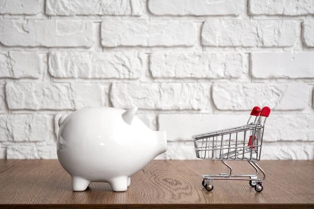 Cofrinho branco e carrinho de compras em um fundo branco. conceito de economia.