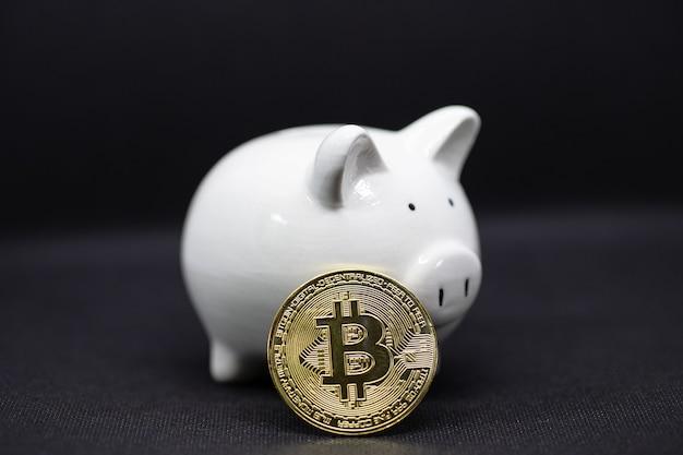 Cofrinho branco e um bitcoin de ouro em um fundo preto para economizar dinheiro, riqueza e conceito de finanças e o copyspace para design.