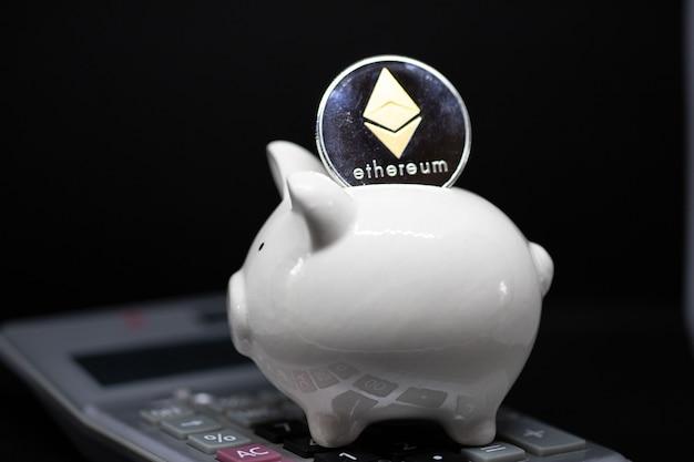 Cofrinho branco e um bitcoin de ouro ficam sobre a calculadora em um fundo preto para economizar dinheiro, riqueza e conceito de finanças e o copyspace para design.