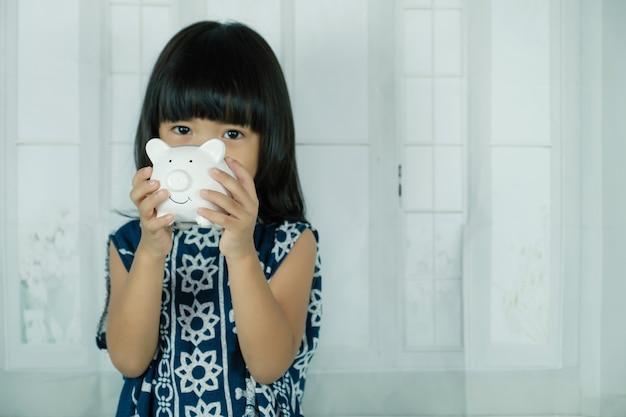 Cofrinho branco na mão da menina asiática, aprenda a economizar para o conceito de futuro.