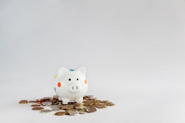 Cofrinho branco ou caixa de dinheiro com moedas de dinheiro.