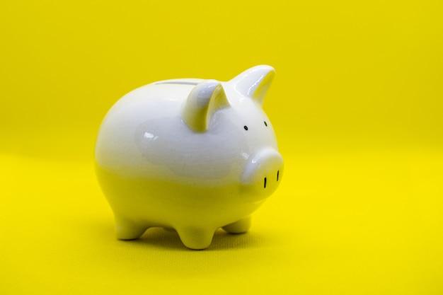Cofrinho branco sobre fundo amarelo e para economizar dinheiro, riqueza e conceito de finanças