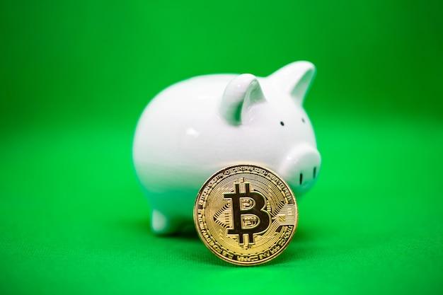 Cofrinho branco sobre um fundo amarelo e um bitcoin de ouro. é um plano de economia para manter o dinheiro e a criptomoeda no futuro.