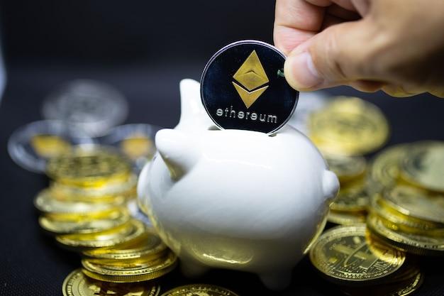 Cofrinho branco sobre um fundo preto e mão humana colocando moeda no cofrinho para economizar dinheiro, riqueza e conceito de finanças e o copyspace para o projeto.