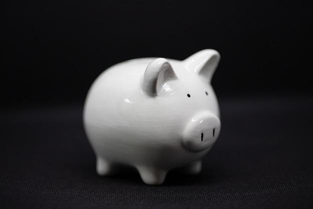 Cofrinho branco sobre um fundo preto. o cofrinho para economizar dinheiro, riqueza e conceito de finanças e o copyspace para design.