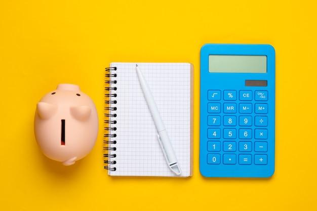 Cofrinho, caderno e calculadora em amarelo