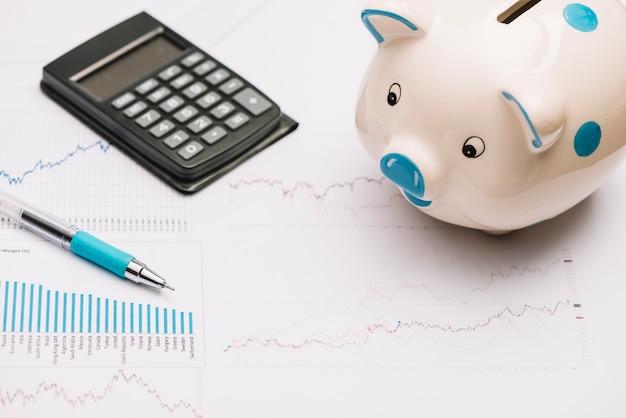 Cofrinho; calculadora e caneta no gráfico do mercado de ações