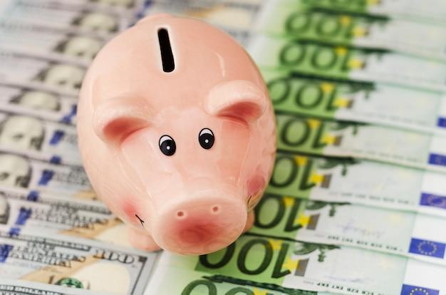 Cofrinho cem notas de dólar e notas de euro de diferentes denominações