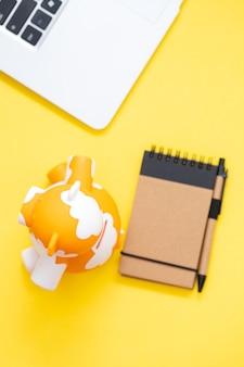 Cofrinho com bloco de notas e computador em fundo amarelo