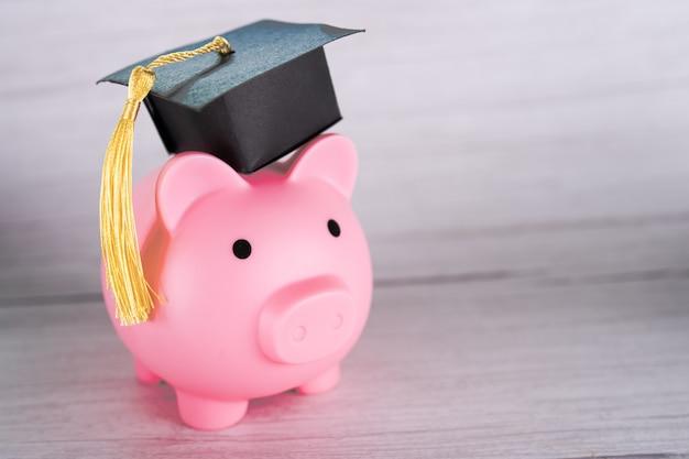 Cofrinho com chapéu de formatura, educação de finanças de negócios economizando dinheiro conceito de bolsa de estudos.