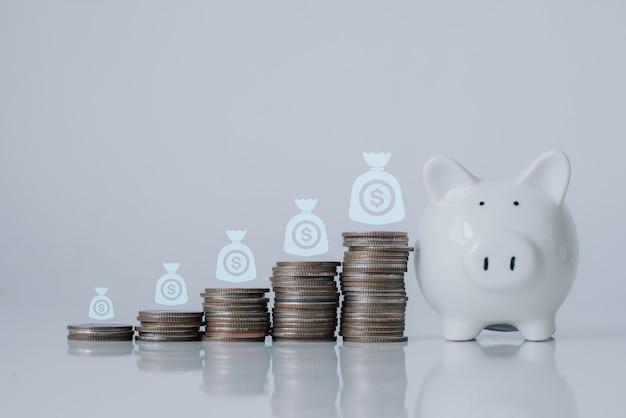 Cofrinho com crescimento de renda positiva da pilha de moedas de dinheiro no chão de madeira branco. investimento, econômico, aposentadoria com espaço de cópia, tamanho do banner, gráfico de crescimento.