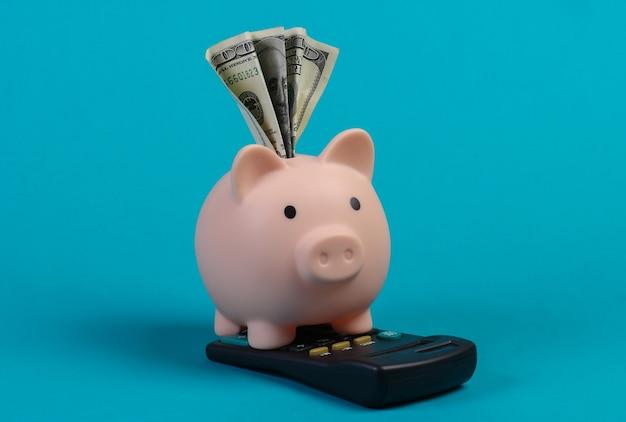 Cofrinho com dólar bil, calculadora na parede azul.